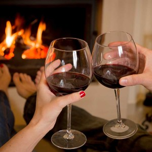 couple drinking wine in front of a fireplace