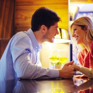couple holding hands over wine