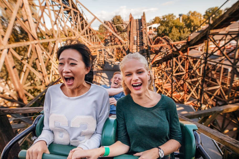 Two young women on a roller coaster with big smiles