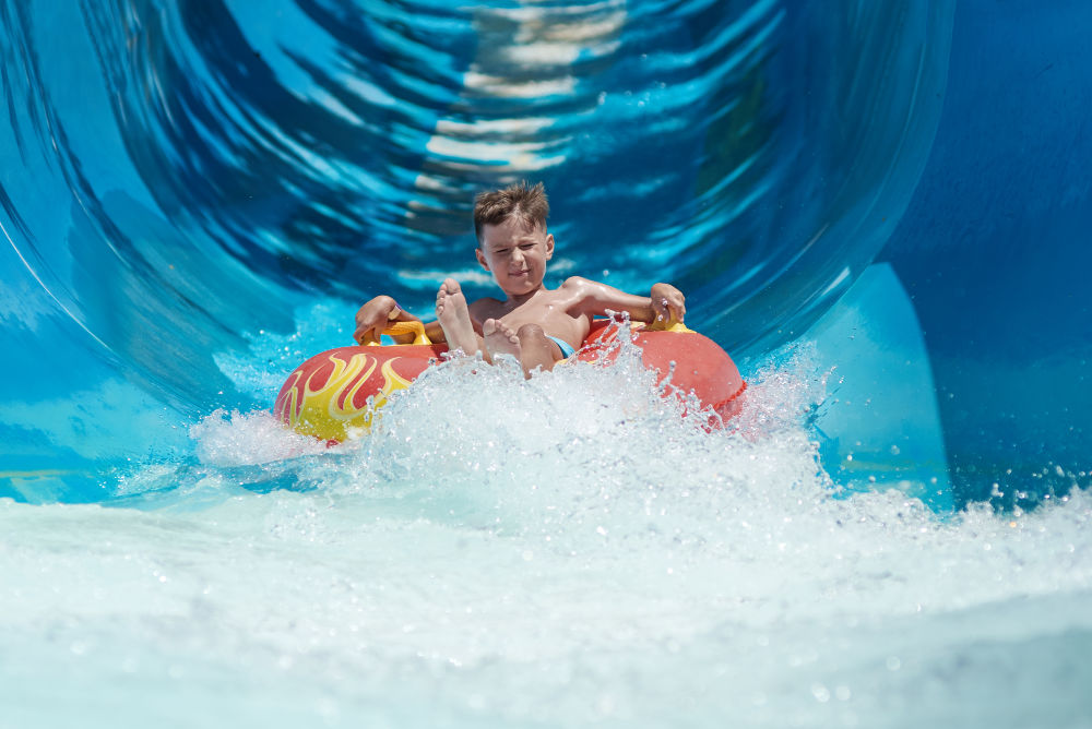 Young boy coming down a water slide on a red and yellow tube
