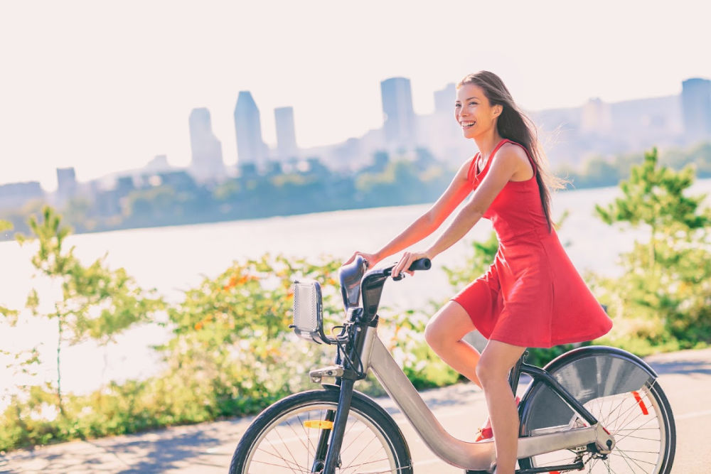 Woman in rad dress on a bike with water and San Antonio behind her