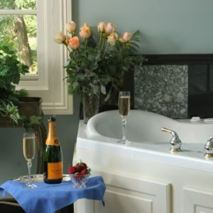Champagne bottle and two glasses near jacuzzi tub